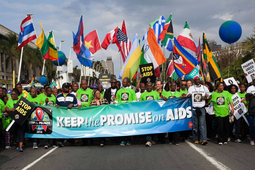 "AIDS activists hold banners and wave flags as they attend a march called ""Keep The Promise 2016"" through the streets of Durban on July 16, 2016. Sixteen years after Nelson Mandela galvanised the world to take up the fight against AIDS, experts and activists return to the South African city of Durban on July 18, seeking to revitalise the fight against the disease."